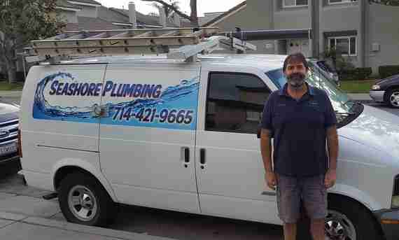 Huntington Beach Plumb about to go to worker standing by work van.